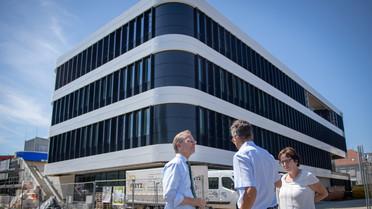 Thomas Rachel, Ulrich Breuer (Kaufmännischer Vorstand des HZDR) sowie Mechthild Krause (Leiterin der Translationale Radioonkologie am OncoRay) vor dem Neubau des NCT Dresden.<br />