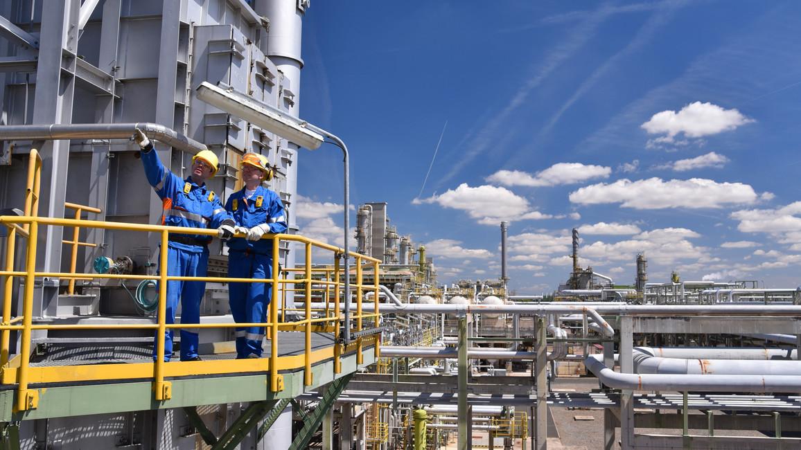 Zwei Industriearbeiter unterhalten sich auf einem Kraftwerksgelände
