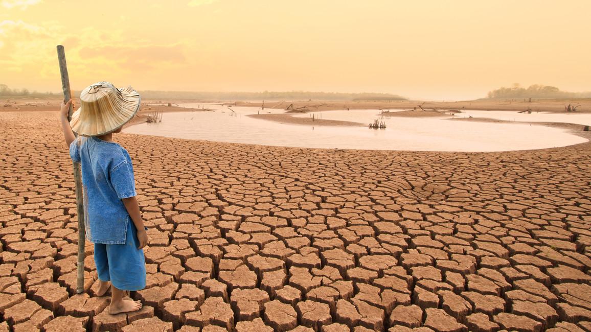 Ein Kind steht auf einer vertrockneten Landfläche.