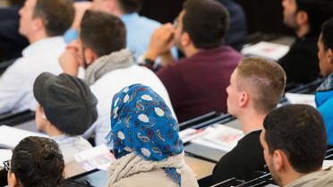 Flüchtlinge sitzen während einer Informationsveranstaltung an der Universität in Hamburg im Hörsaal.