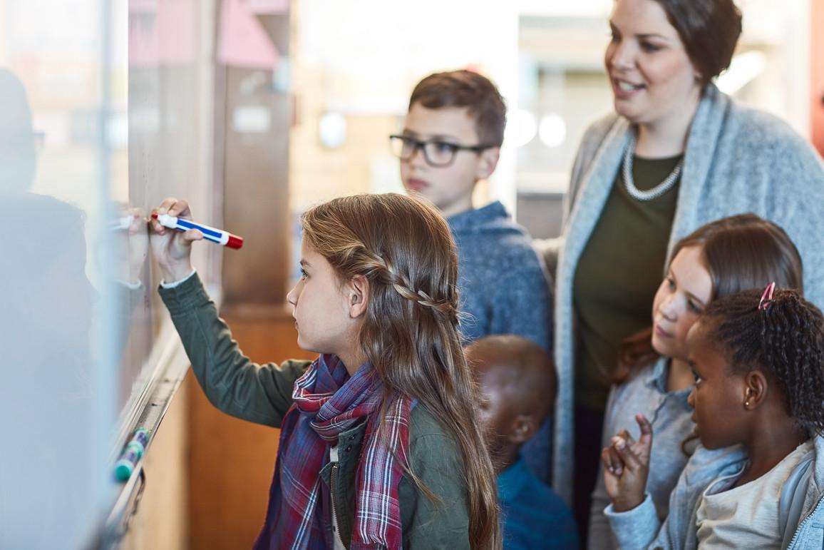Schülerin schreibt auf einem Whiteboard