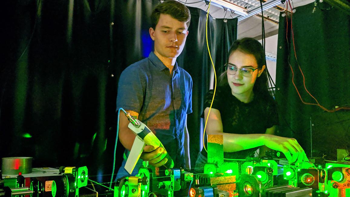 Zwei junge Forschende stellen die Laserstärke für ein Experiment ein.