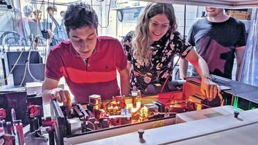 Zwei junge Forschende richten Laser für ein Experiment aus.