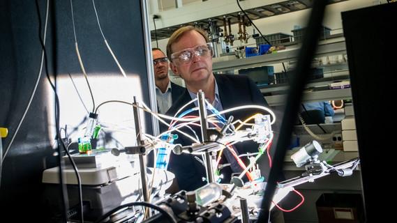 Der Parlamentarische Staatssekretär Thomas Rachel betrachtet eine Photokatalyseanlage.