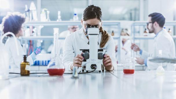 Wissenschaftlerin im Labor, die durch ein Mikroskop schaut