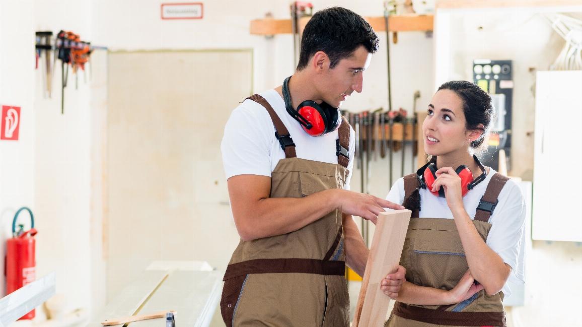 Tischler und Auszubildende arbeiten gemeinsam in Werkstatt