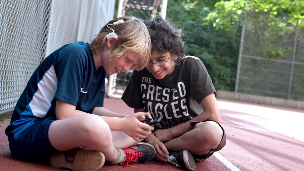 Zwei Jungen schauen auf Smartphone. Ein Junge trägt ein Hörgerät.