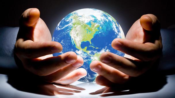 Zwei Hände halten schützend unseren Planeten.