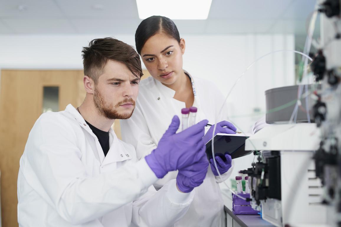 Wissenschaftler mit Kollegin im Labor untersuchen Proben