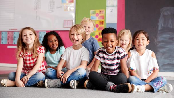Lachende Schülerinnen und Schüler sitzen auf dem Fußboden eines Klassenzimmers.