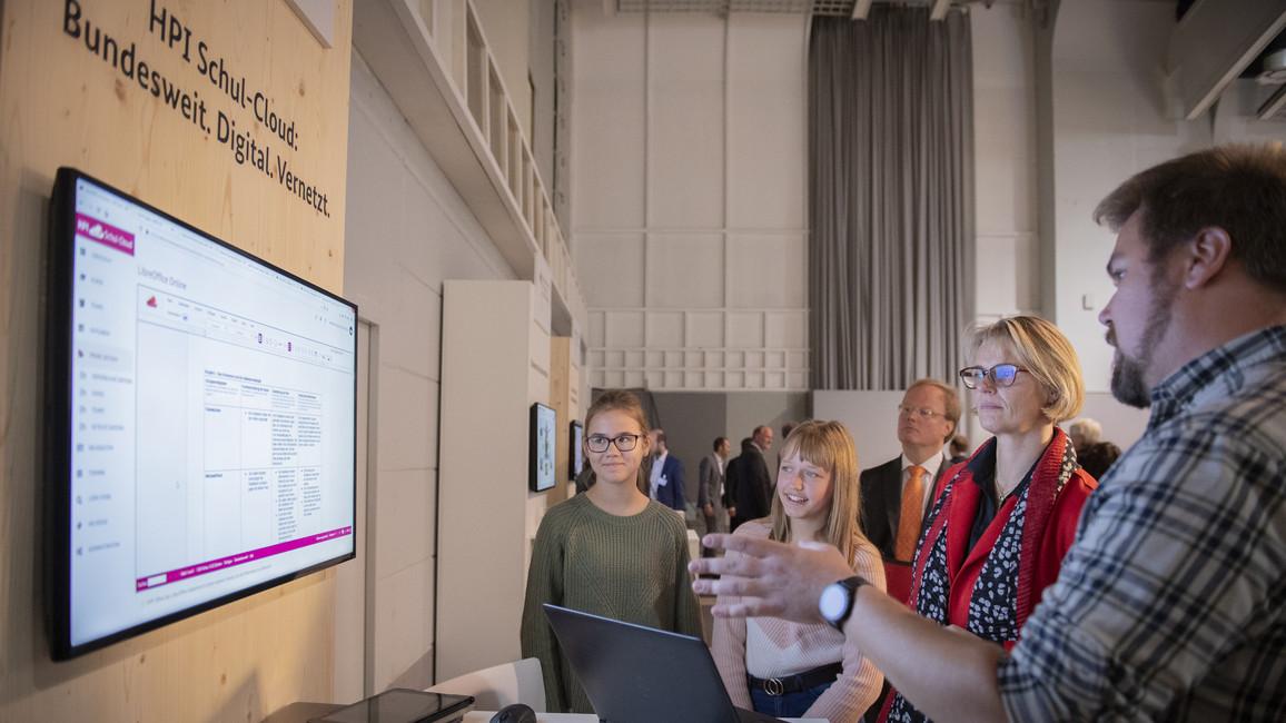 Anja Karliczek informiert sich im Gespräch mit zwei Schülerinnen und einem Lehrer über ihre Arbeit und Erfahrungen mit der Schul-Cloud.