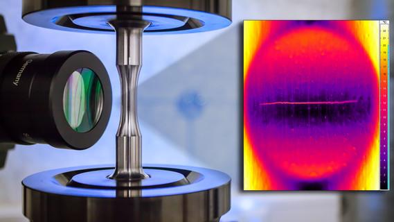 Auf der linken Seite des Bildes ist eine Thermokamera zu sehen, die auf Materialprobe gerichtet ist. Die rechte Seite zeigt die thermografische Aufnahme der Probe mit sichtbarer Materialschädigung (Hot-Spot-Bildung und Rissausweitung).