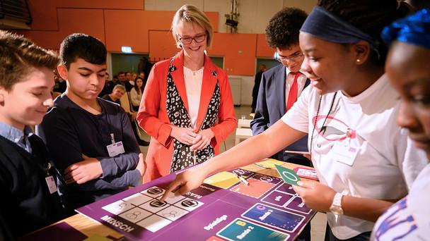 'Das Brettspiel ermöglicht es – gerade aufgrund seiner analogen Form – das hochkomplexe maschinelle Lernen verständlich darzustellen. Wir werden daher 150 weitere Klassensätze produzieren lassen, damit mehr Schulen in Deutschland von diesem Angebot profitieren können.', kündigte Bundesministerin Anja Karliczek an.