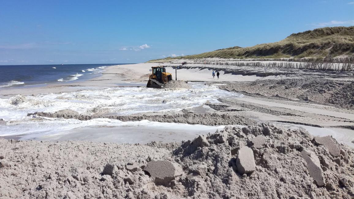 Der Sand wird aus dem Meer an Land gespült und dort mit Planierraupen verteilt.
