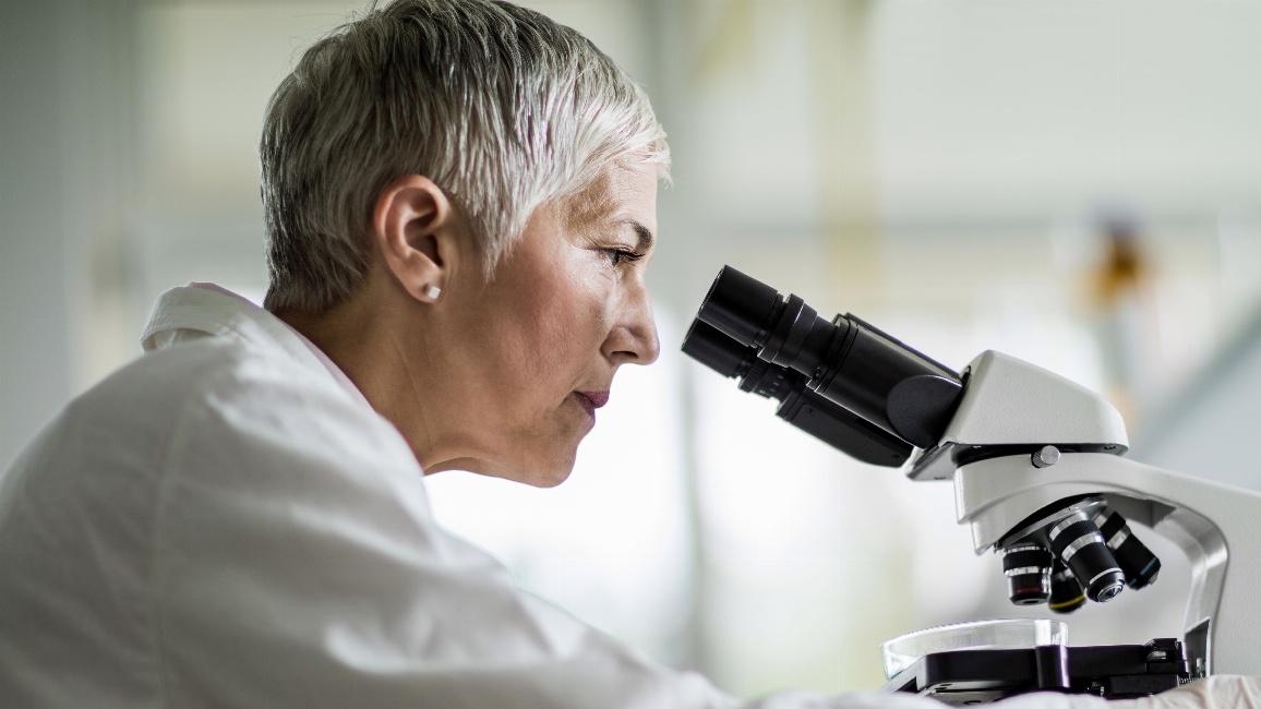 Wissenschaftlerin blickt durch ein Mikroskop