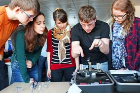Mitarbeiter erklärt Studierenden eine Appartur