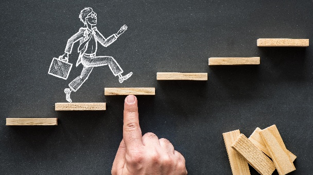 Eine auf einer Tafel gezeichnete Person mit Aktentasche steigt eine Treppe hinauf. Eine Stufe wird von einer Hand an die richtige Position in der Treppe geschoben.