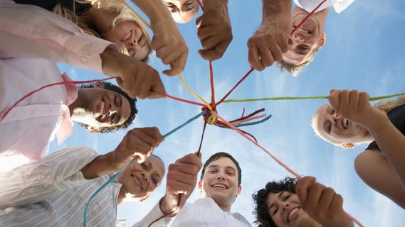 Eine Gruppe von Menschen halten eine Schnur zusammen.