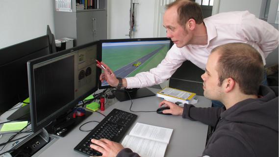 Das Bild zeigt Prof. Dr.-Ing. Reiner Kriesten und einen Studierenden vor einem Computermonitor bei der Analyse der modellbasierten Reichweitensimulation.