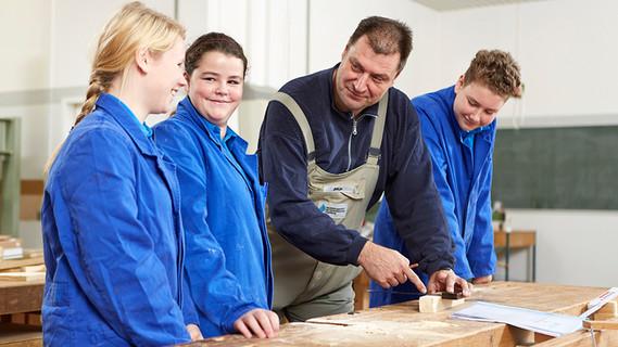 Schülerinnen und Schüler mit Ausbilder an der Werkbank im Rahmen der Werkstatttage des Berufsorientierungsprogramms des BMBF