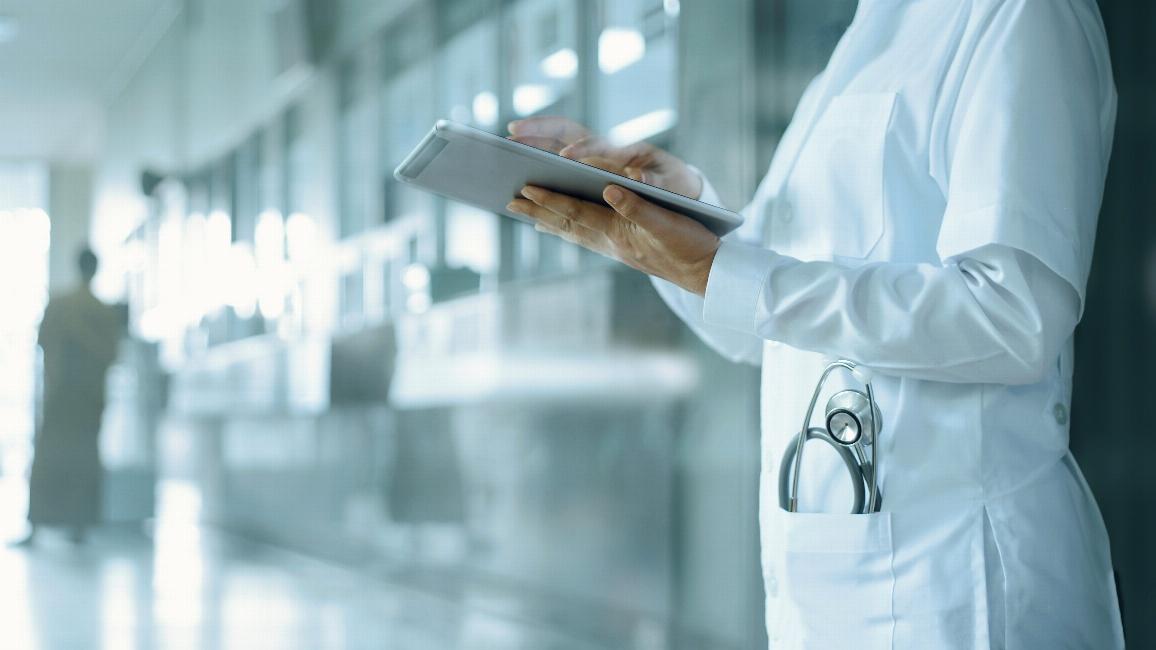 Ärztin die mit Tablet in der Hand auf Krankenhausflur steht