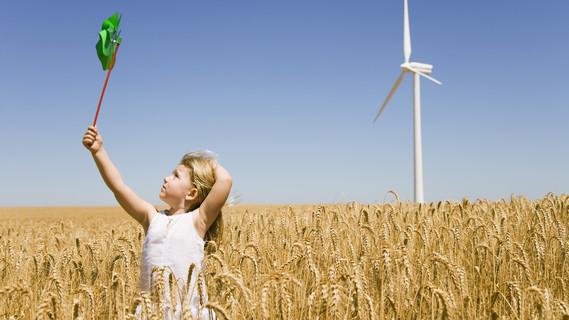 Mädchen spielt einem Feld (im Hintergrund ein Windrad)