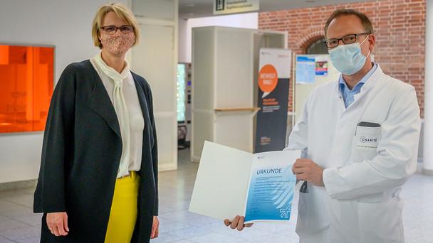 Bundesministerin Anja Karliczek überreicht Herrn Prof. Dr. Martin Witzenrath,Stellvertretender Klinikdirektor der Medizinischen Klinik mit Schwerpunkt Infektiologie und Pneumologie, eine Förderurkunde des BMBF.