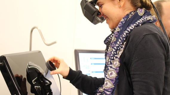 Junge Frau trägt Virtual-Reality-Brille vor Monitor mit Gesichtskontur