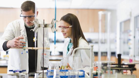 Ein Dozent demonstriert einer Studentin ein Experiment