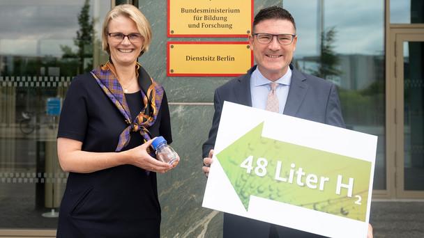 """Bundesforschungsministerin Anja Karliczek, Innovationsbeauftragter """"Grüner Wasserstoff"""" Dr. Stefan Kaufmann:Kleines Fläschchen, große Wirkung - In diesen 80 ml Flüssigkeit (LOHC) sind 48 Liter Wasserstoff gebunden. Ausreichend Energie, um einen Kühlschrank einen Tag lang zu versorgen."""