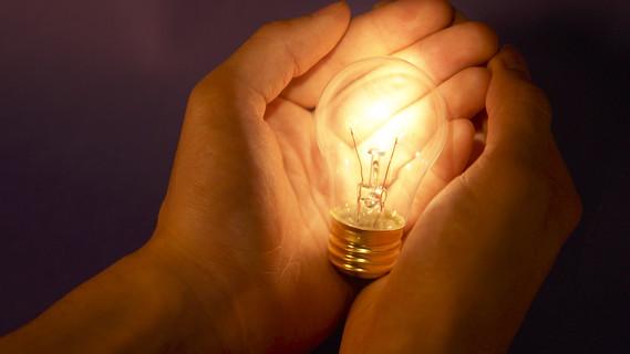 Zwei Hände umfassen eine leuchtende Glühlampe