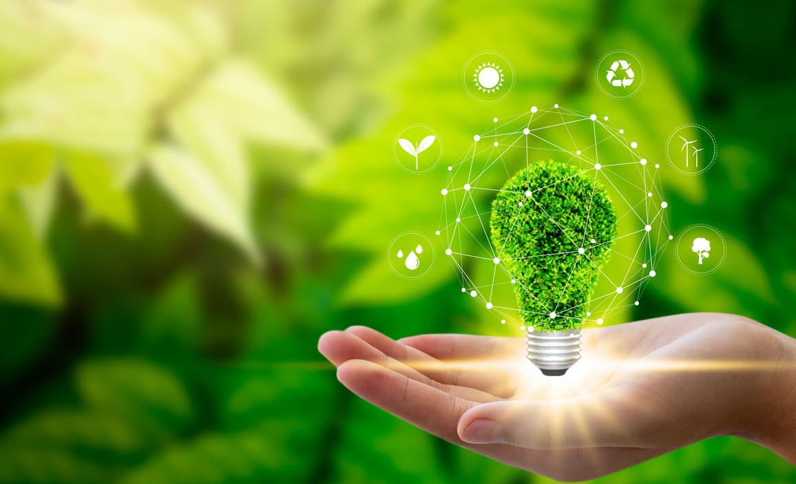Hand hält grüne Glühbirne mit Symbolen für erneuerbare Energiequellen