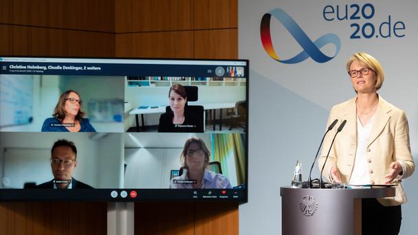 Ministerin Karliczek steht während der Pressekonferenz an einem Pult. Im Hintergrund sind die per Skype zugeschalteten Wissenschaftler zu sehen.
