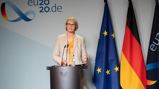 Ministerin Karliczek steht an einem Rednerpult, im Hintergrund ist die deutsche und die europäische Flagge zu sehen.