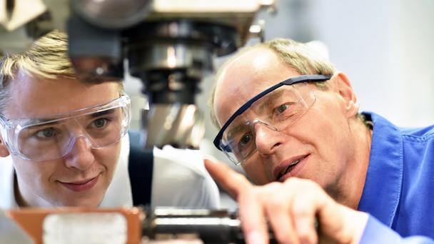 Berufsausbildung im Handwerk: Jugendlicher und Lehrer an einer CNC Maschine