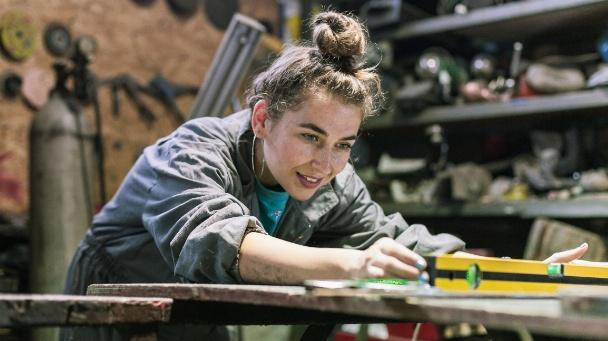 Junge Frau arbeitet in der Werkstatt
