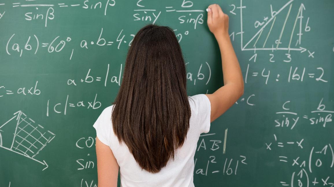Schülerin schreibt Formeln an die Tafel