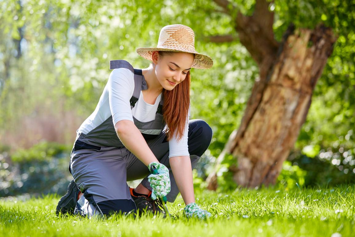 Junge Frau arbeitet zur Frühlingszeit im Garten