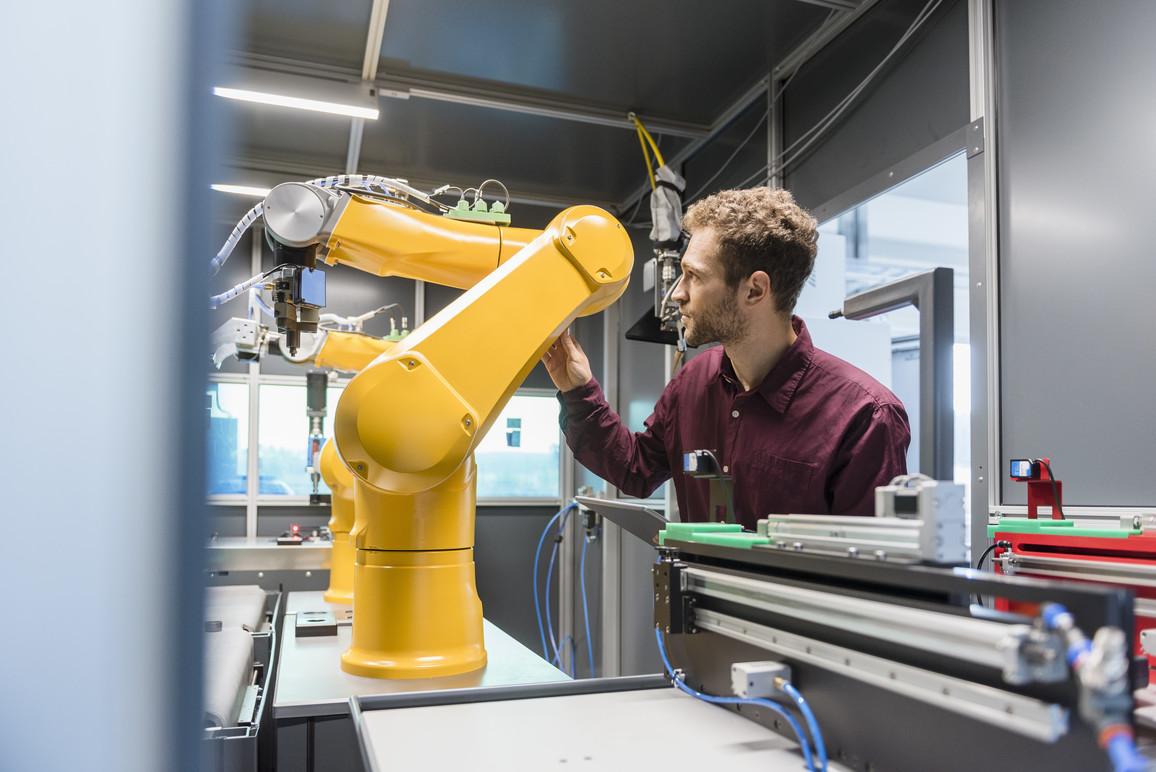 Geschäftsmann prüft Industrieroboter in der High-Tech-Firma