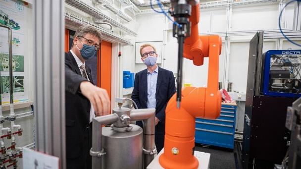 PETRA III-Leiter Christian Schroer erklärt Staatssekretär Wolf-Dieter Lukas (r.) die PETRA III-Messstation P11, an der auch Experimente zu Wirkstoffen gegen Covid-19 stattfinden.