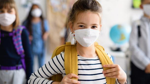 Mädchen mit Gesichtsmaske geht nach Covid-19-Quarantäne und Sperrung wieder zur Schule.
