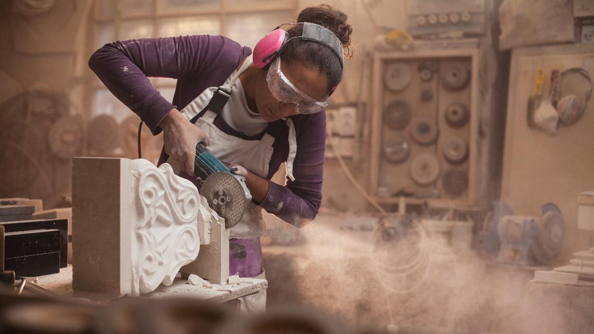 Steinmetzin, die ein Stück weißen Marmor in einer Werkstatt schneidet