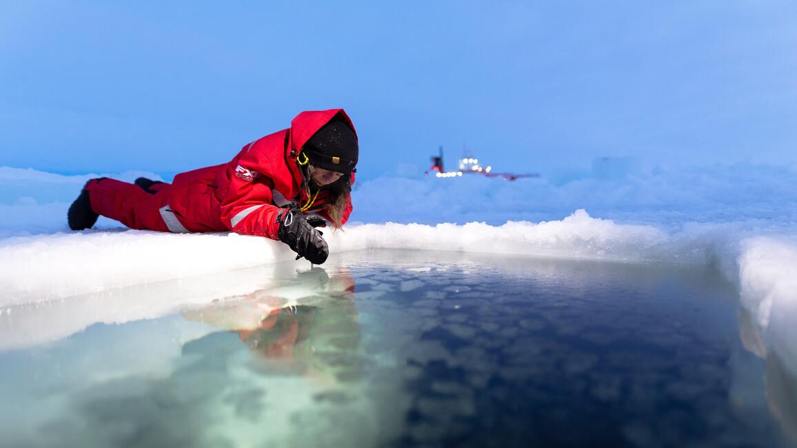 Ein Polarforscher entnimmt Wasserproben aus einem Loch im Eis.