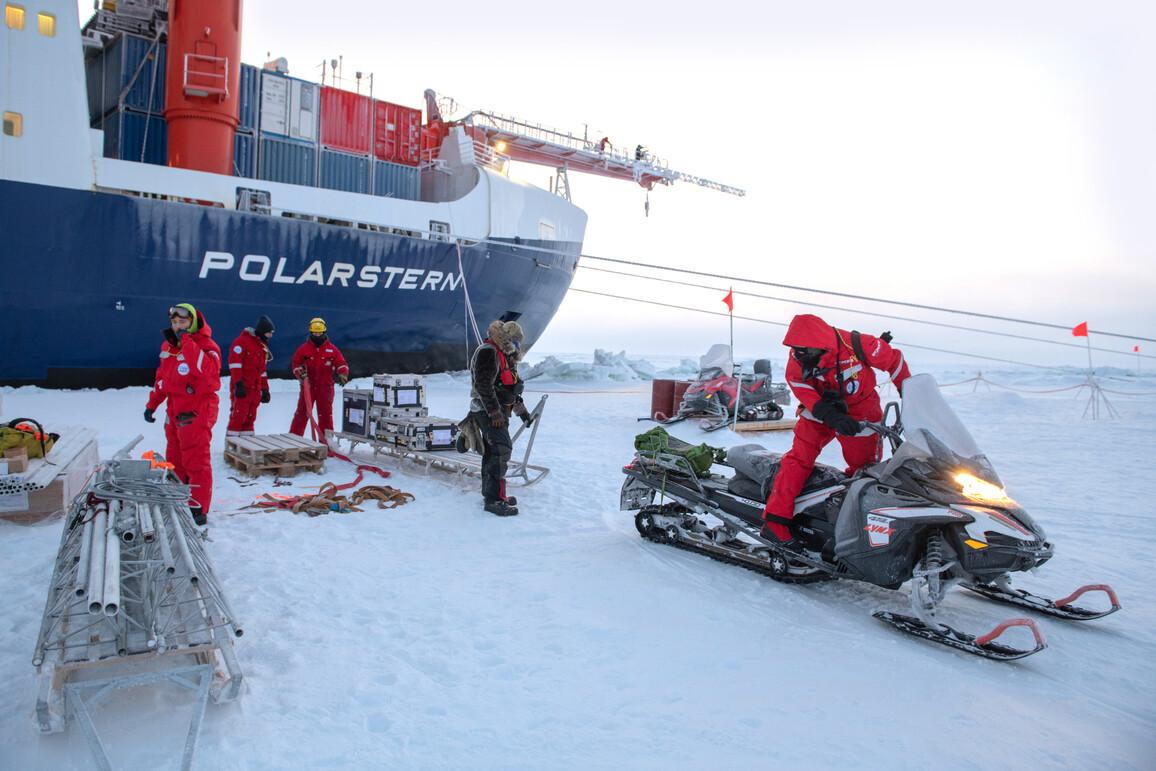 """Forscher mit Schlitten und Schneemobil vor dem Expeditionsschiff """"Polarstern"""" in der Arktis."""