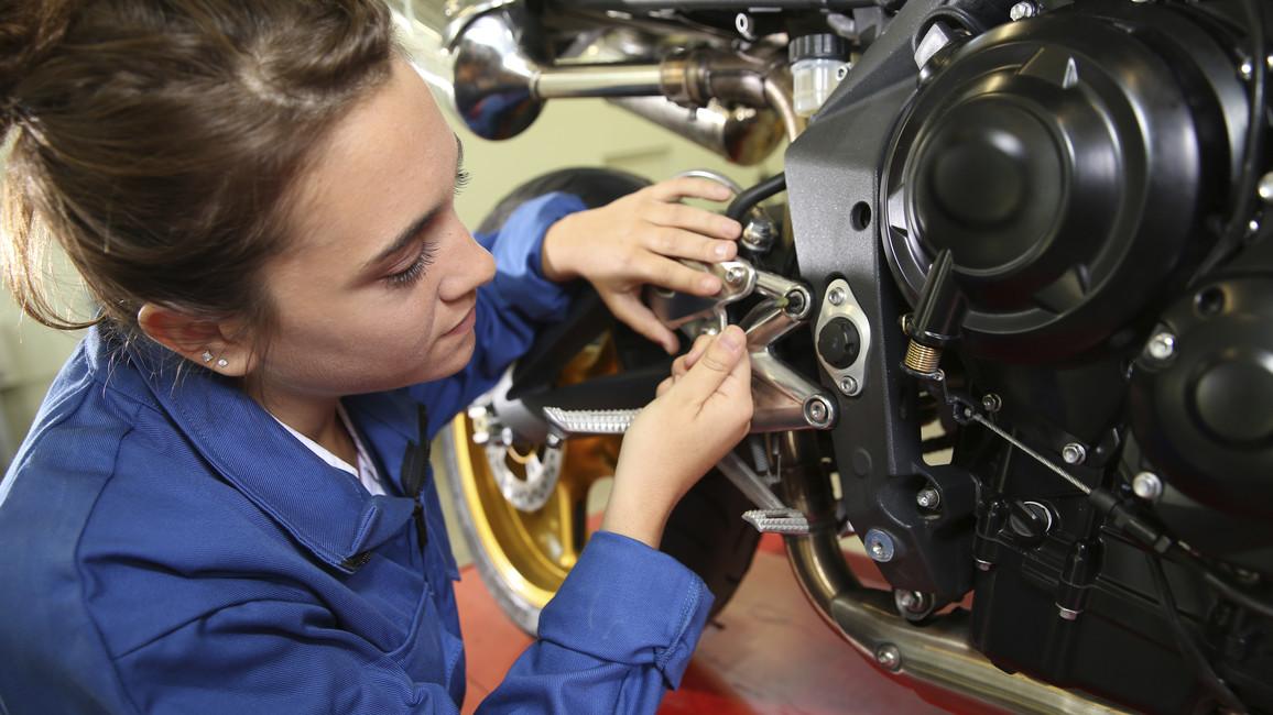 Eine Auszubildende arbeitet an einem Motorrad