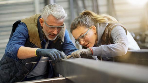 Metallarbeiter mit Lehrling in der Werkstatt