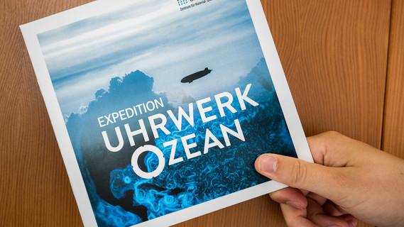 Eine Hand hält eine Publikation zum Experiment 'Uhrwerk Ozean'