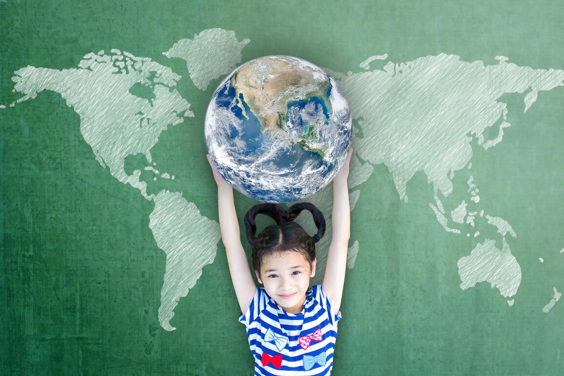 Mädchen hält die Weltkugel hoch