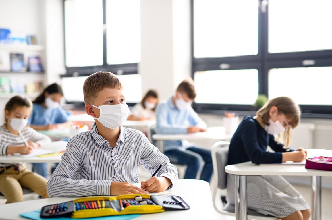 Kinder mit Gesichtsmaske zurück in der Schule nach Quarantäne
