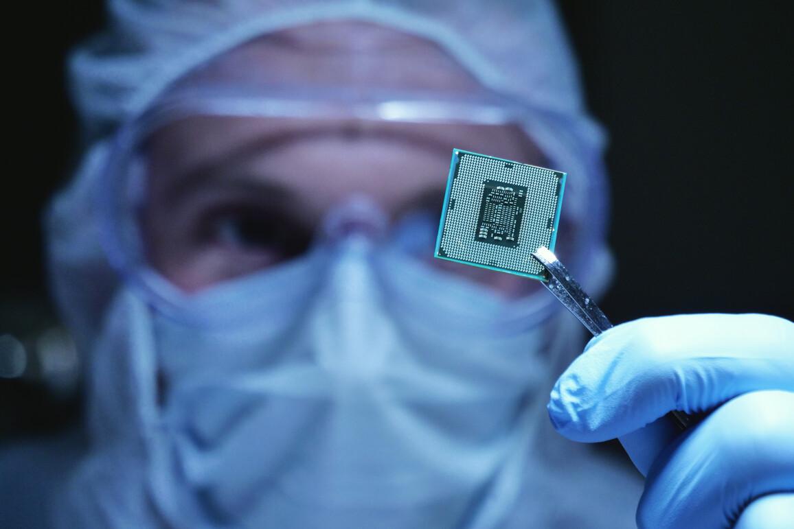 Konstruktionsingenieur im sterilen Overall hält Mikrochip